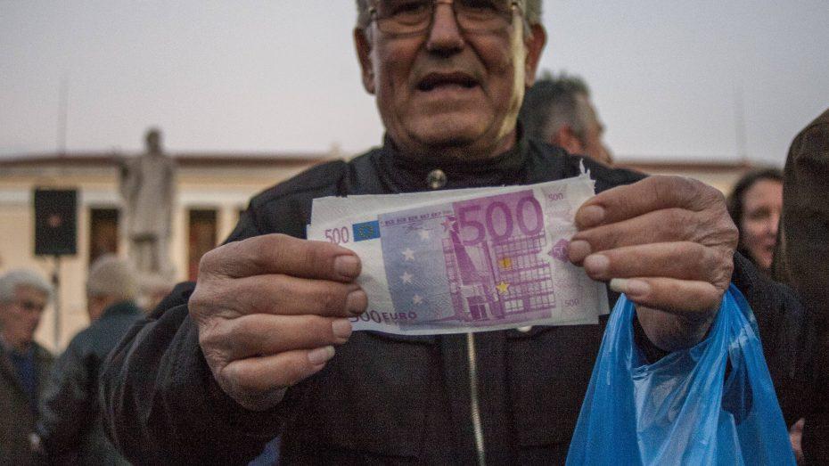Bei einer Demonstration in Athen hält ein protestierender Rentner einen gefälschten 500-Euro-Schein in der Hand. (Foto: Imago/Pacific Press Agency)